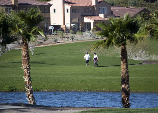 A couple walks near the entrance of Lake Las Vegas east of Henderson as seen Friday. March 7,2014. The new owners of the 3,592 acre master planned community around a 320 acre artificial lake are r ...