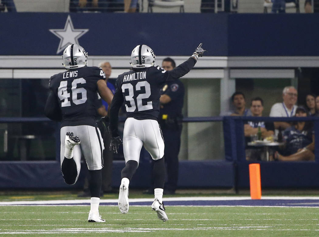 Oakland Raiders' LaTroy Lewis (46) and Antonio Hamilton (32) celebrate an interception by Lewis he ran back for a touchdown against the Dallas Cowboys in the second half of a preseason NFL footbal ...