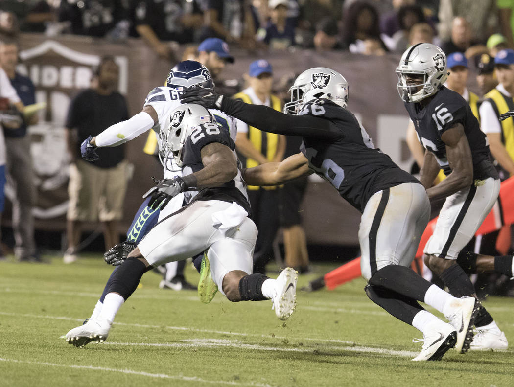 Oakland Raiders safety Shalom Luani (26) tries to tackle Seattle Seahawks wide receiver Cyril Grayson (13) on a special teams play at a NFL preseason game in Oakland, Calif., Thursday, Aug. 31, 20 ...