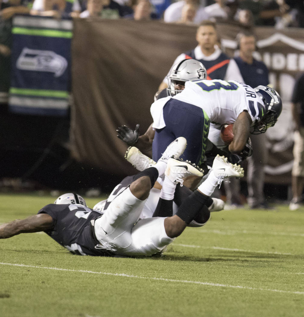 Seattle Seahawks wide receiver Cyril Grayson (13) hurdles over Oakland Raiders defenders in the first half of their preseason game in Oakland, Calif., Thursday, Aug. 31, 2017. Heidi Fang Las Vegas ...