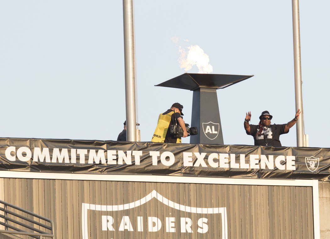 The mother of Oakland Raiders running back Marshawn Lynch's, Delisa Lynch, lights the Al Davis torch prior to the start of a preseason game against the Seattle Seahawks in Oakland, Calif., Thursda ...