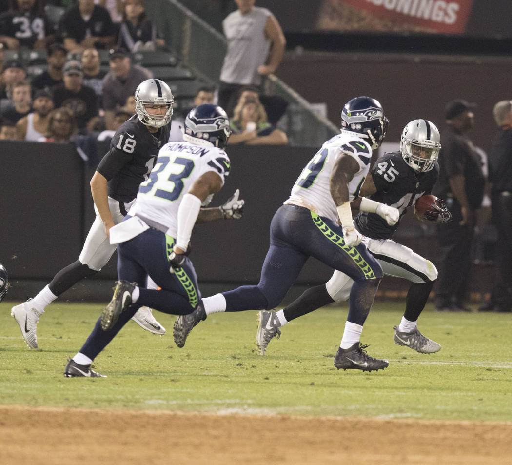 Oakland Raiders running back George Atkinson (45) runs with the ball against Seattle Seahawks defenders in the first half of their preseason game in Oakland, Calif., Thursday, Aug. 31, 2017. Heidi ...