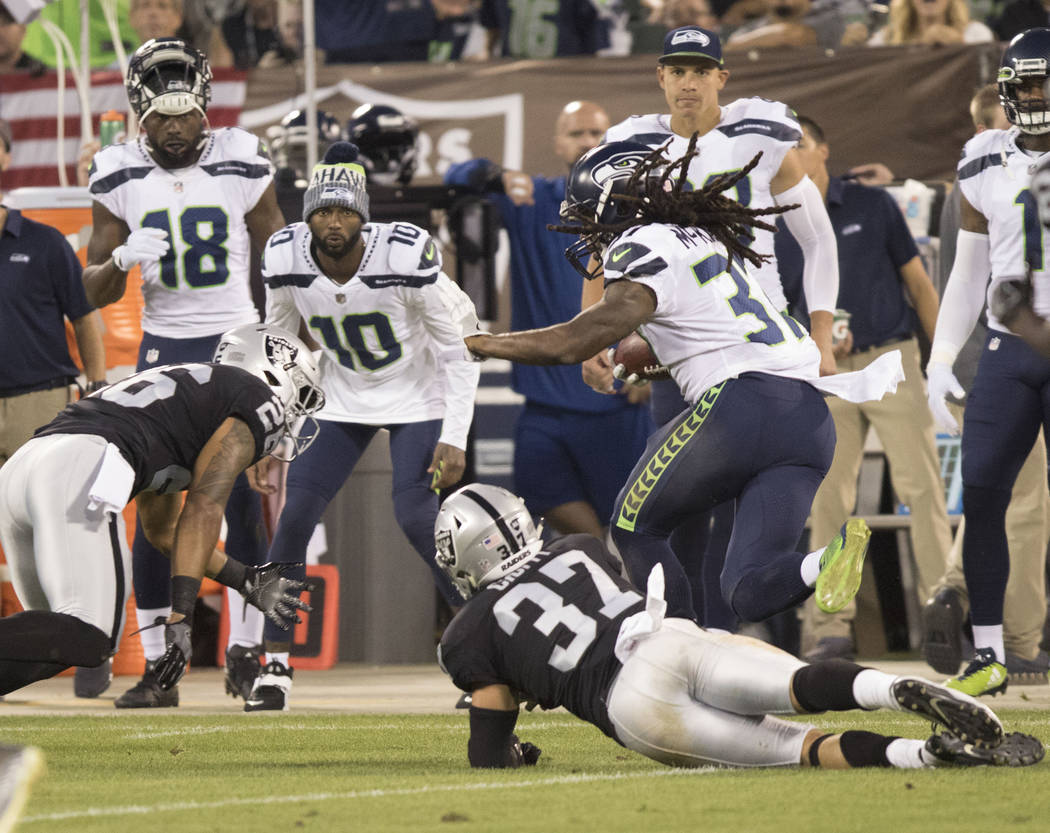 Oakland Raiders defenders try to tackle Seattle Seahawks defensive back Bradley McDougald (30) on a punt return in the first half of their preseason game in Oakland, Calif., Thursday, Aug. 31, 201 ...