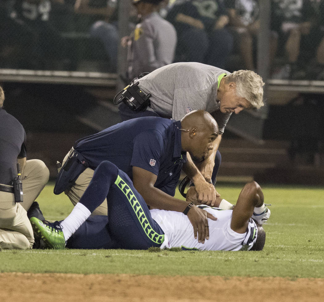 Seattle Seahawks cornerback DeAndre Elliott (21) is hurt after a play as a trainer and head coach Pete Carroll check on him in the first half of the preseason game in Oakland, Calif., Thursday, Au ...