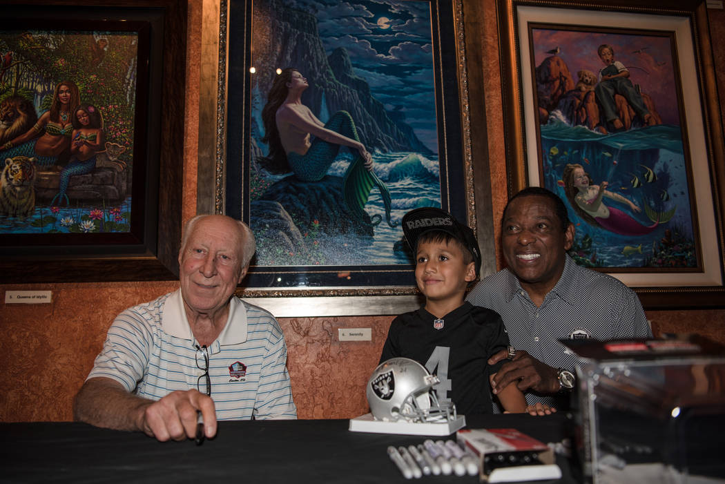Former Raiders' wide receivers Fred Biletnikoff and Cliff Branch take a photo with Jaiden Wahnetah-Fanjul, 4, at the Mermaid Lounge at Silverton hotel-casino on Saturday, Sep. 9, 2017, in Las Vega ...