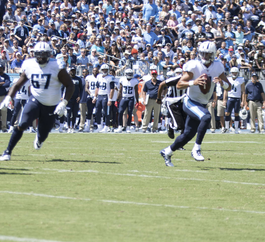 Tennessee Titans quarterback Marcus Mariota (8) scrambles with the football in the first half of the game against the Oakland Raiders at the Nissan Stadium in Nashville, Tenn., Sunday, Sept. 10, 2 ...