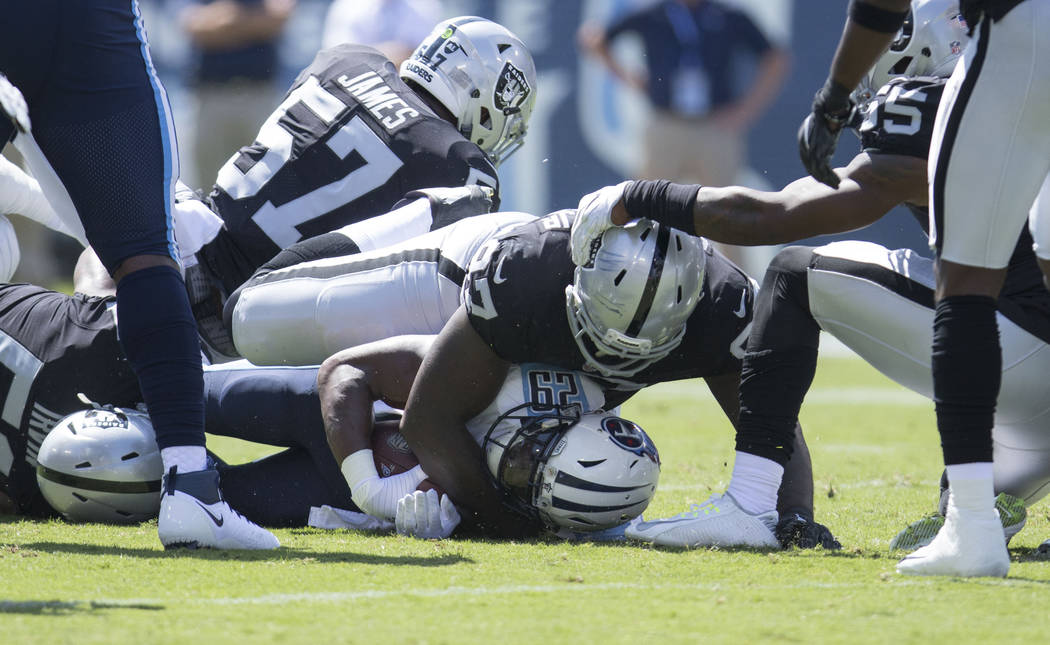 Tennessee Titans running back DeMarco Murray (29) is tackled by Oakland Raiders defensive end Mario Edwards (97) in the first half of their game against the Oakland Raiders at the Nissan Stadium i ...