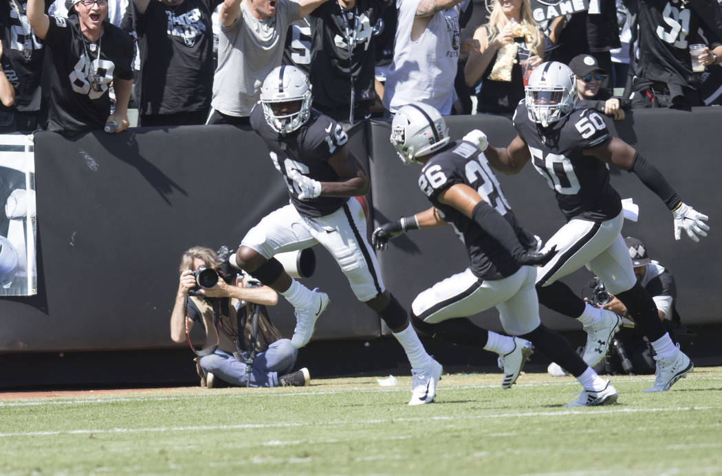 Oakland Raiders wide receiver Johnny Holton (16) celebrates with safety Shalom Luani (26) and linebacker Nicholas Morrow (50) after recovering a muffed punt in the first half of their game against ...