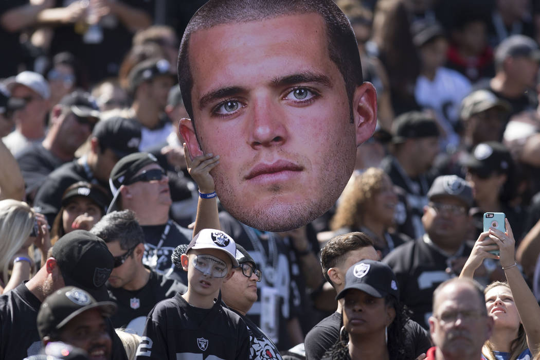 A cut out of Oakland Raiders quarterback Derek Carr (4) is held up by fans in the Oakland-Alameda County Coliseum during the team's game against the New York Jets in Oakland, Calif., Sunday, Sept. ...