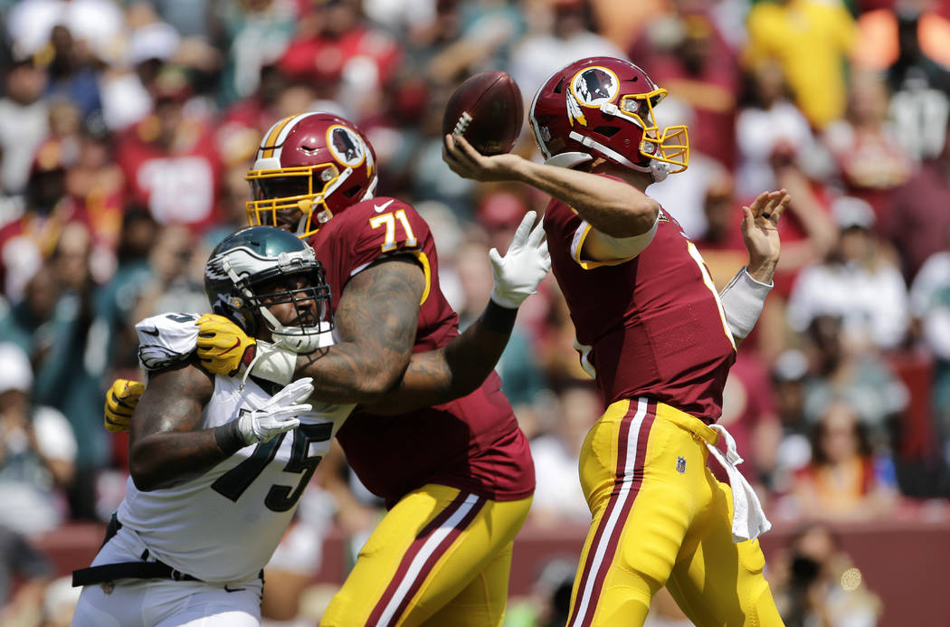 Philadelphia Eagles defensive end Vinny Curry, left, tries to get past Washington Redskins offensive tackle Trent Williams as Redskins quarterback Kirk Cousins, right, throws to a receiver in the  ...