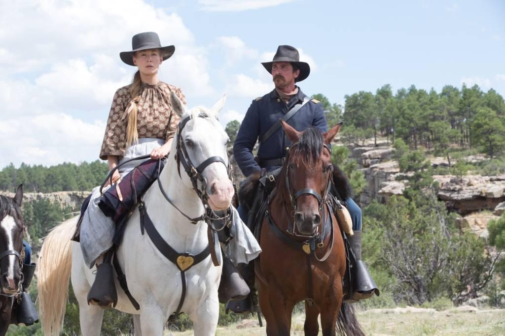 "Recently widowed Rosalee Quaid (Rosamund Pike) rides alongside Joseph Blocker (Christian Bale) in a scene from ""Hostiles."" (Lorey Sebastian/Yellow Hawk, Inc.)"
