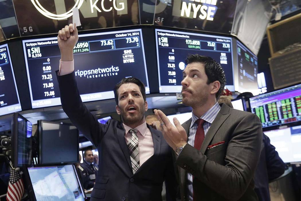 """In this Oct. 14, 2014, file photo, Jonathan Scott, left, and Drew Scott, of HGTV's """"Property Brothers"""" cable television show, mimic traders as they visit the post that handles Scripps Networks Int ..."""