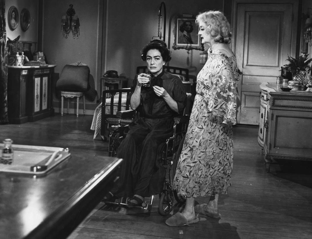 """Actress Joan Crawford, sits in wheelchair as actress Bette Davis stands next to her at the set in a scene while filming """"What Ever Happenend To Baby Jane"""" in Hollywood, USA, Augu ..."""