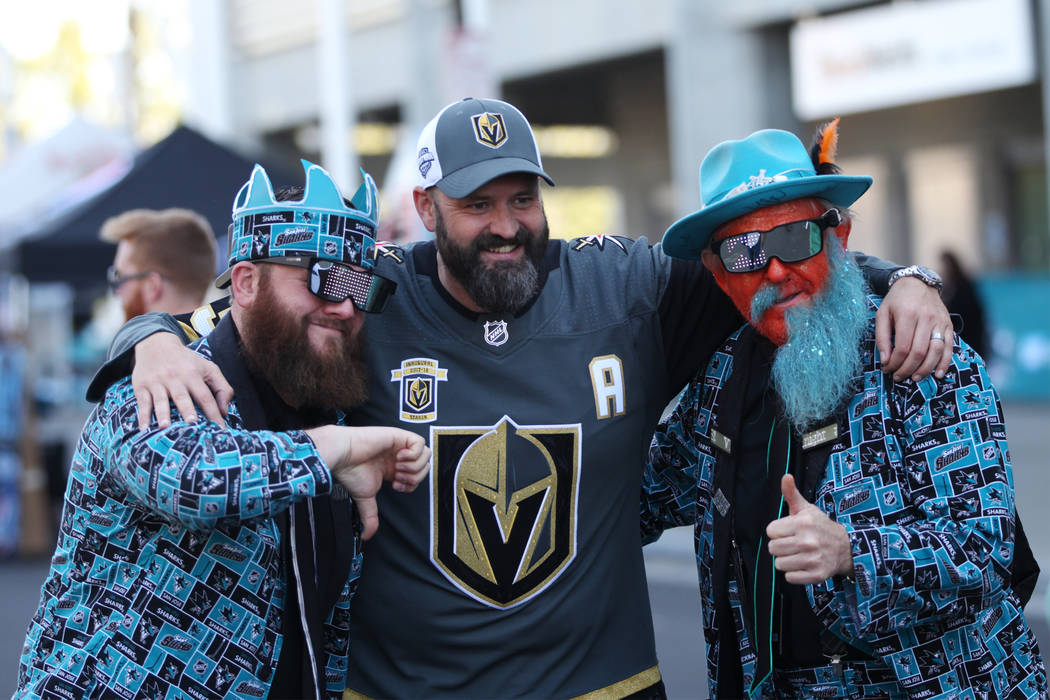 San Jose Sharks fans Rick Cady, left, and Anthony Mattos, right, take a photo with Vegas Golden Knights fan Wolfgang Gastner before Game 4 of an NHL hockey second-round playoff series at the SAP C ...