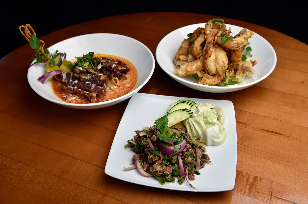 Featured menu items from left, crispy duck khao soi, khoa soi and garlic prawns are displayed at Lotus of Siam restaurant on Friday, May 11, 2018, in Las Vegas. David Becker/Las Vegas Review-Journ ...