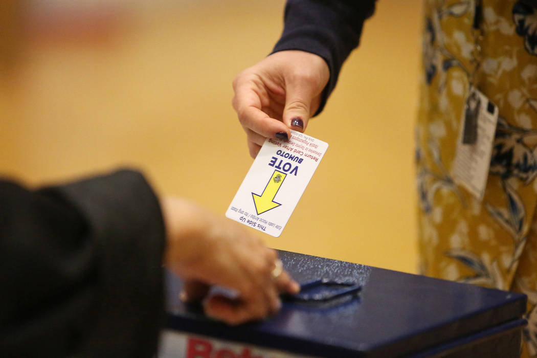 A voter returns a voting card after casting her ballots at a polling station at Historic Fifth Street School in Las Vegas, Tuesday, Nov. 6, 2018. (Caroline Brehman/Las Vegas Review-Journal)