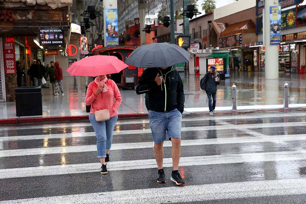 People cross Fourth Street at the Fremont Street Experience in downtown Las Vegas during a light rain in January. The valley can expect a cloudy Wednesday and more rain on Thursday. (K.M. Cannon/L ...