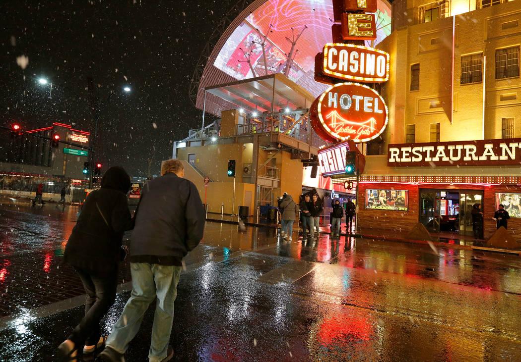 Pedestrians walk as snow falls in downtown Las Vegas, Wednesday, Feb. 20, 2019. (Chitose Suzuki / Las Vegas Review-Journal) @chitosephoto