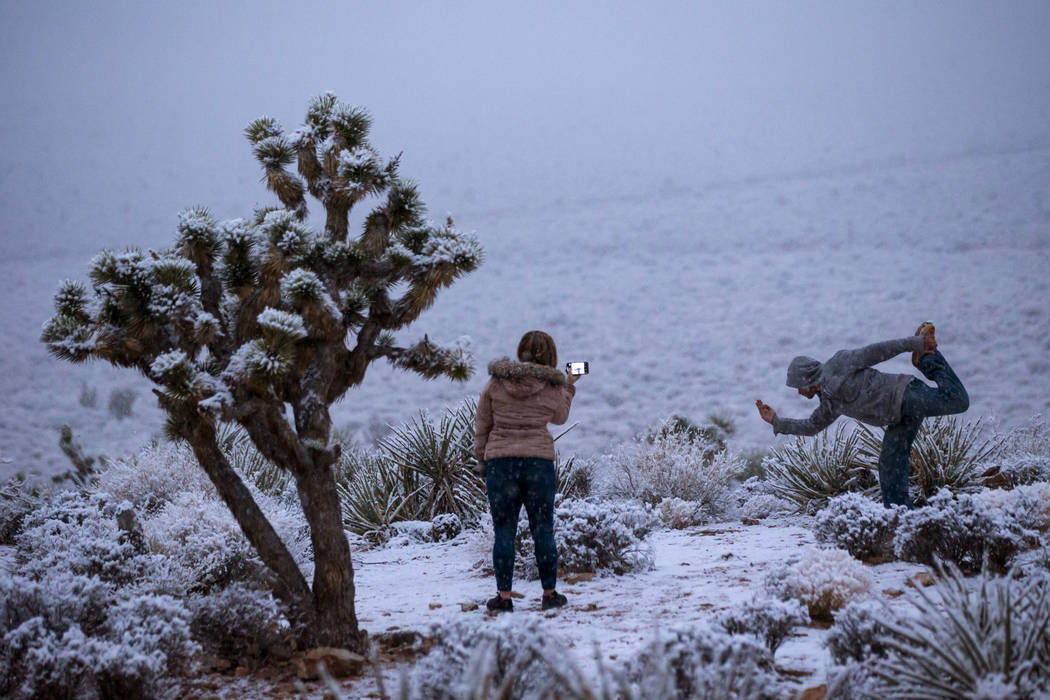 James Minner of Las Vegas, right, poses as Candace Reid of Albuquerque, N.M., records while snow falls around the overlook at the Red Rock Canyon National Conservation Area outside of Las Vegas on ...