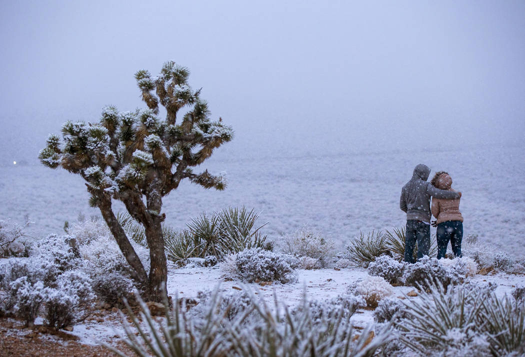 James Minner, of Las Vegas, left, and Candace Reid, of Albuquerque, N.M., watch as snow falls around the overlook at the Red Rock Canyon National Conservation Area outside of Las Vegas on Wednesda ...