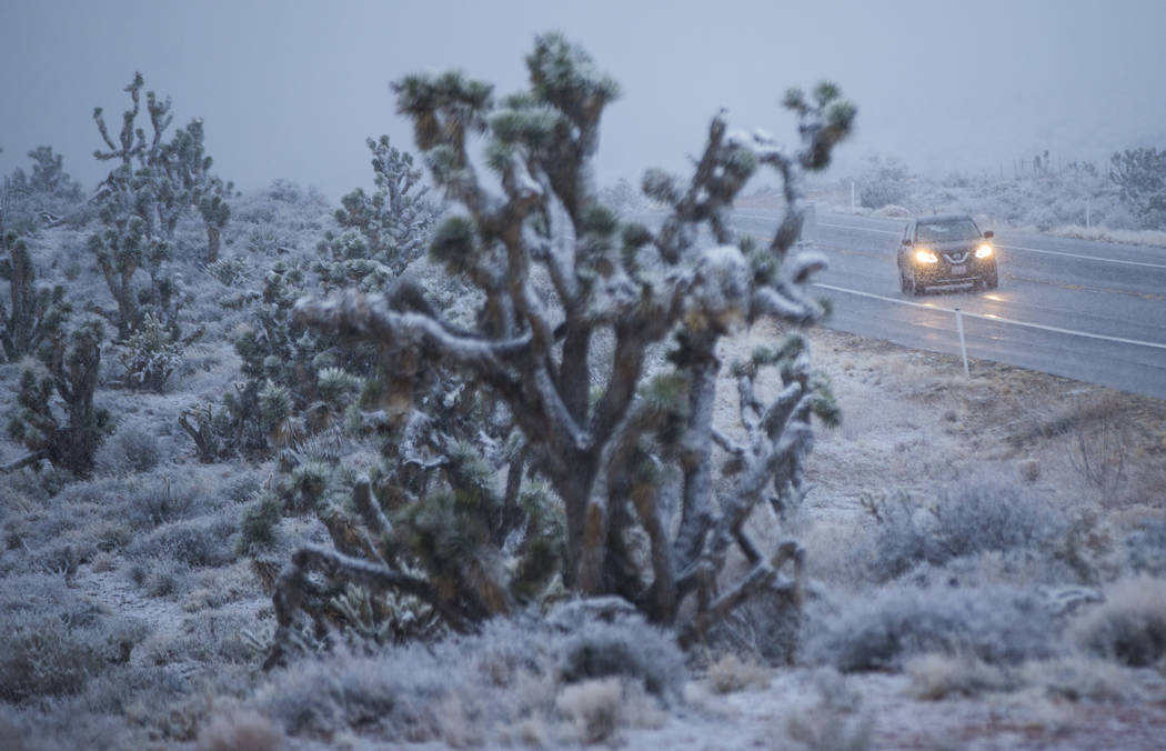 An SUV drives along state Route 159 as snow falls around the Red Rock Canyon National Conservation Area outside of Las Vegas on Wednesday, Feb. 20, 2019. (Chase Stevens/Las Vegas Review-Journal) @ ...