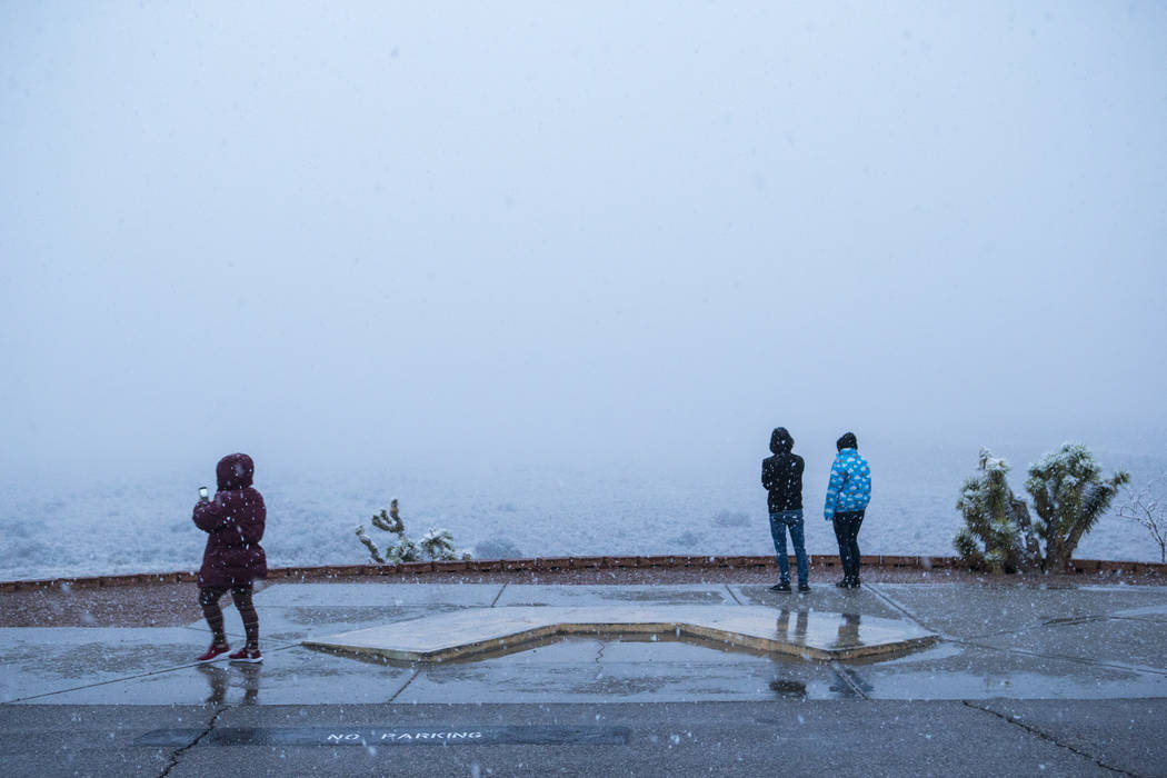 People watch as snow falls around the overlook at the Red Rock Canyon National Conservation Area outside of Las Vegas on Wednesday, Feb. 20, 2019. (Chase Stevens/Las Vegas Review-Journal) @cssteve ...