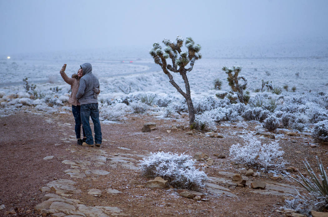 Candace Reid, of Albuquerque, N.M., left, takes a selfie with James Minner, of Las Vegas, as snow falls around the overlook at the Red Rock Canyon National Conservation Area outside of Las Vegas o ...