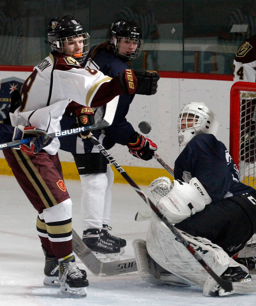 Faith Lutheran's Matty Johnson (8) tries to control the puck against Utah's goalie Landon Palmer, left, during the first period of a hockey game at the City National Arena in Las Vegas, Saturday, ...