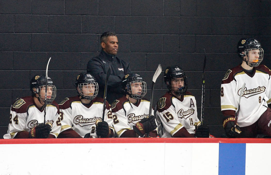 Faith Lutheran's head coach Pokey Roddick, center, watches the hockey game with his players against Utah during the second period at the City National Arena in Las Vegas, Saturday, Dec. 15, 2018. ...