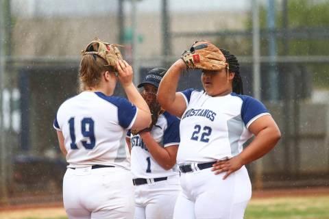 Shadow Ridge's Sydney Morgan (19), Kyanna Galvan (1) and Alyssa Stanley (22) cover their faces as their softball game against Centennial is delayed due to rain at Shadow Ridge High School in Las V ...