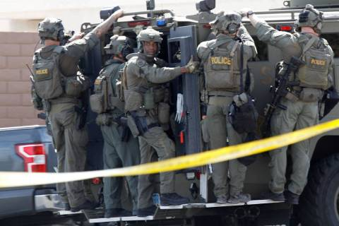 A SWAT vehicle carries a Metropolitan Police Department SWAT team during a barricade situation near Grand Teton and Durango in the northwest area of the Las Vegas valley, Saturday, March 23, 2019. ...