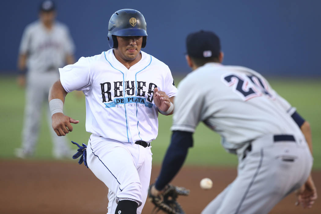 Las Vegas 51s' Phillip Evans returns to first base to avoid being tagged out by the Colorado Sp ...