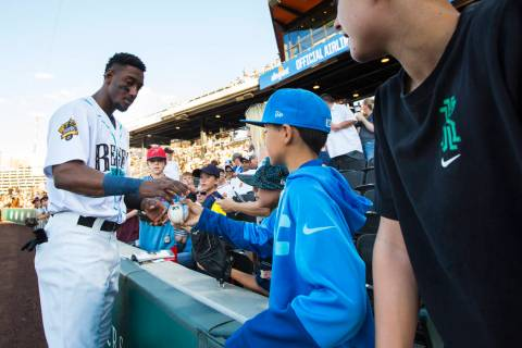 Las Vegas Aviators shortstop Jorge Mateo signs items for a group of young fans before the start ...