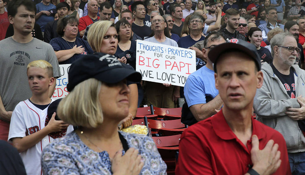 A fan holds a sign sending thought and prayers to former Boston Red Sox designated hitter David ...