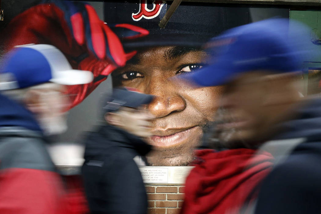 In this Oct. 1, 2016, file photo, fans at walk past a photograph of Boston Red Sox's David Orti ...