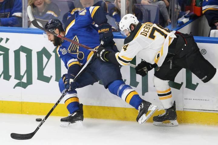 Boston Bruins left wing Jake DeBrusk (74) tries to stop St. Louis Blues defenseman Robert Bortu ...