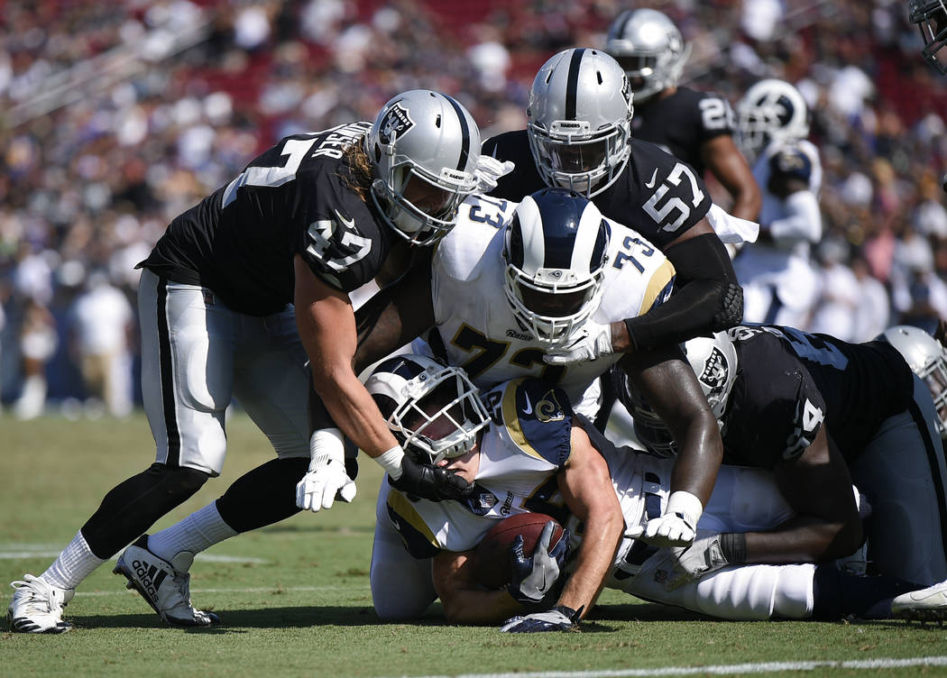 Los Angeles Rams running back Nick Holley runs the ball defended by Oakland Raiders linebacker ...