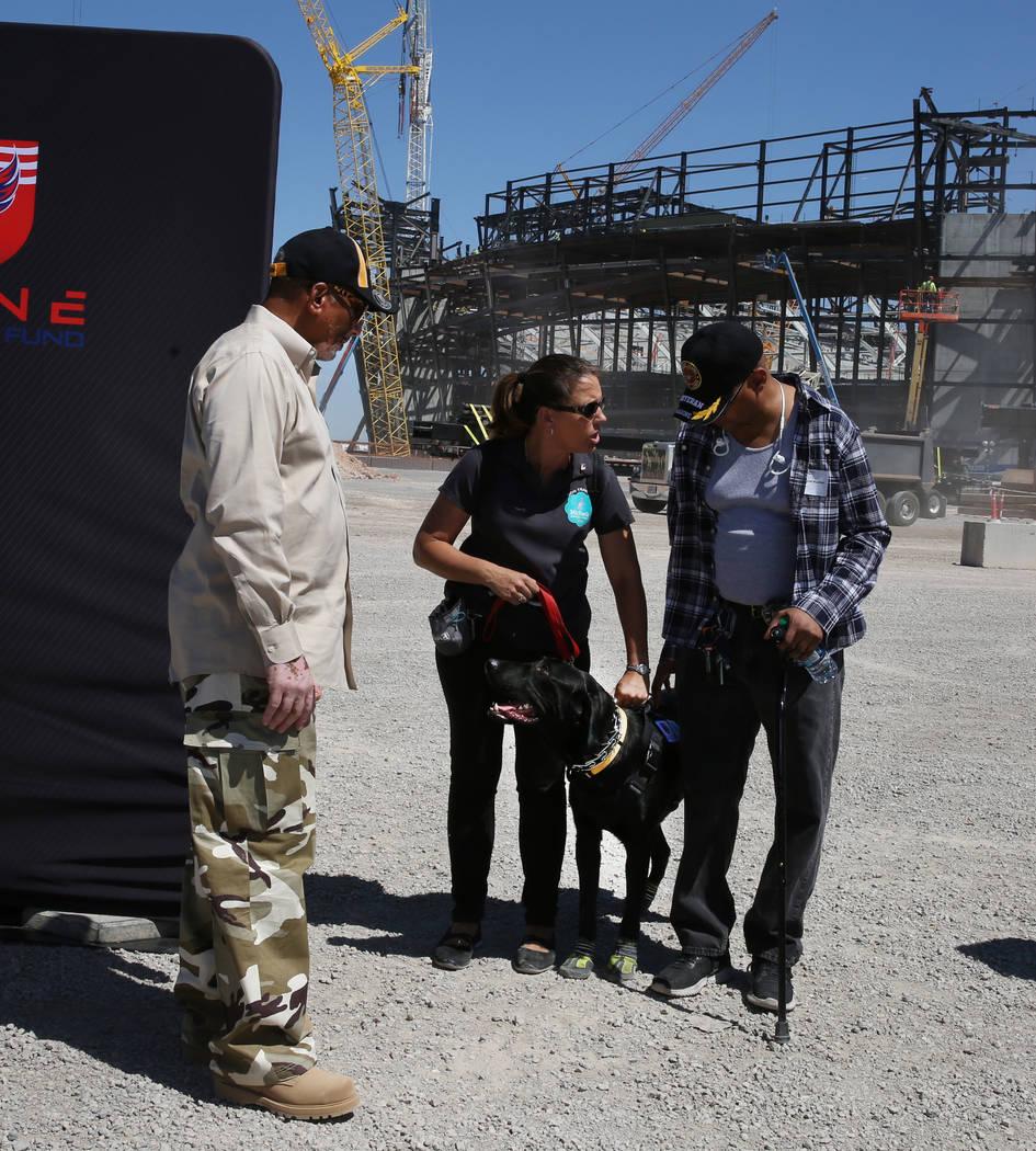 Stephenie Gerken, Michael's Angel Paws executive director, holding a service dog, Shaddo ...
