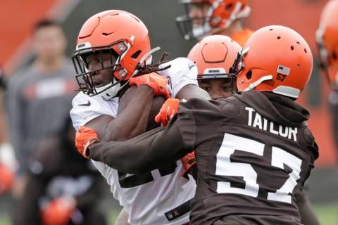 Cleveland Browns running back Kareem Hunt, left, breaks a tackle by linebacker Adarius Taylor d ...