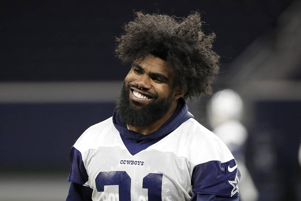 Dallas Cowboys running back Ezekiel Elliott smiles as he walks off the field after participatin ...