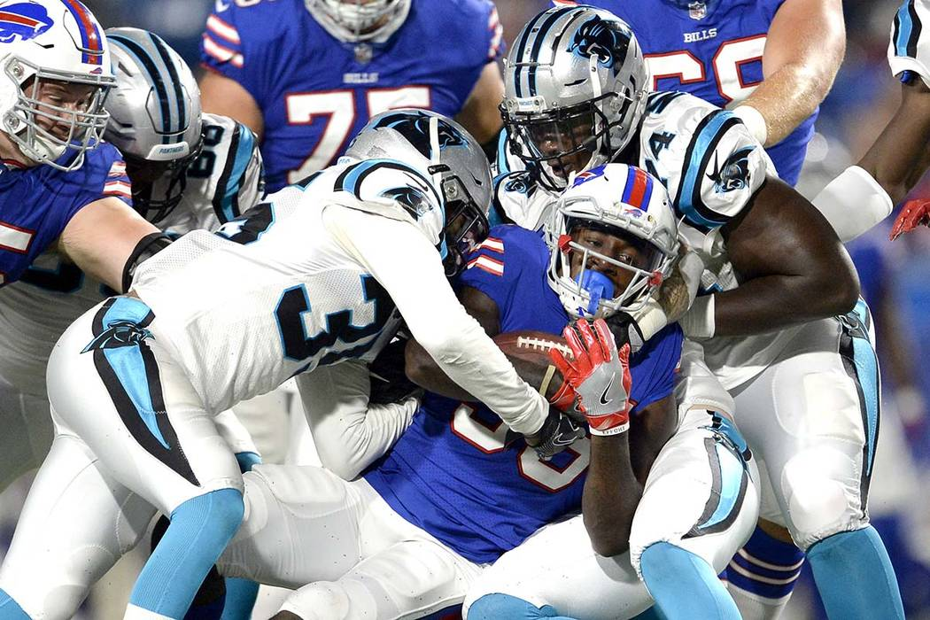 Buffalo Bills running back Keith Ford, center, is tackled by Carolina Panthers cornerback Corn ...