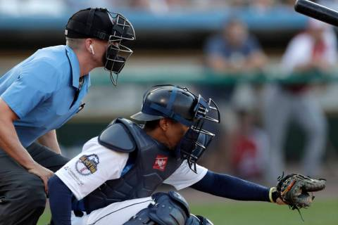 Home plate umpire Brian deBrauwere, left, huddles behind Freedom Division catcher James Skelton ...