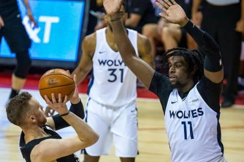 Brooklyn Nets guard Dzanan Musa, left, falls back on a shot attempt as Minnesota Timberwolves c ...