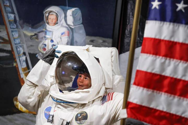 Visitors pose for photos beside a portrait of Neil Armstrong at the Armstrong Air and Space Mus ...