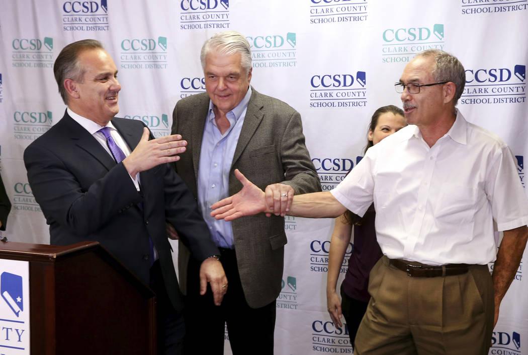 Gov. Steve Sisolak prods Clark County School District Superintendent Jesus Jara, left, and John ...