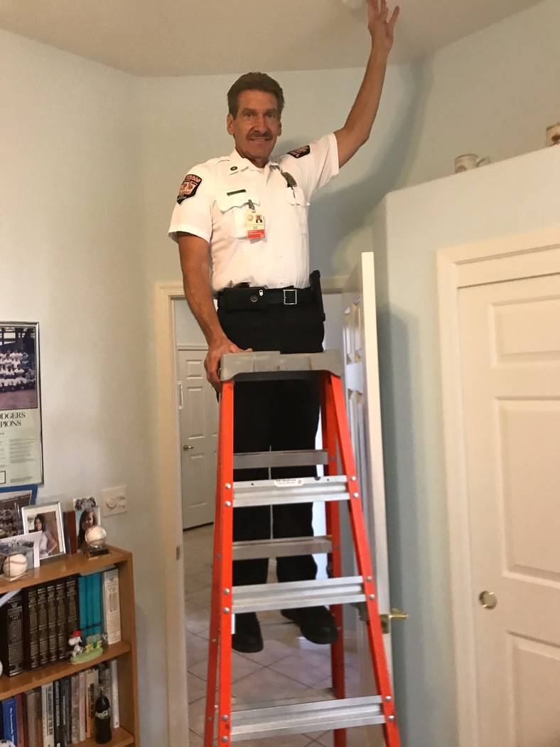 Fire Inspector Dave Marsili checks a smoke alarm after it was installed. (Herb Jaffe)