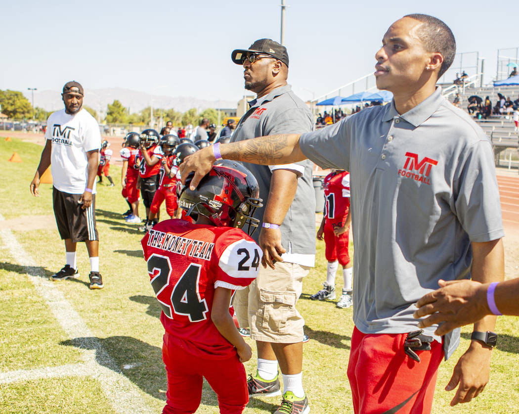 Devin Conway pats the helmet of TMT Red Lion player Justice Banks, 8, during a youth football g ...