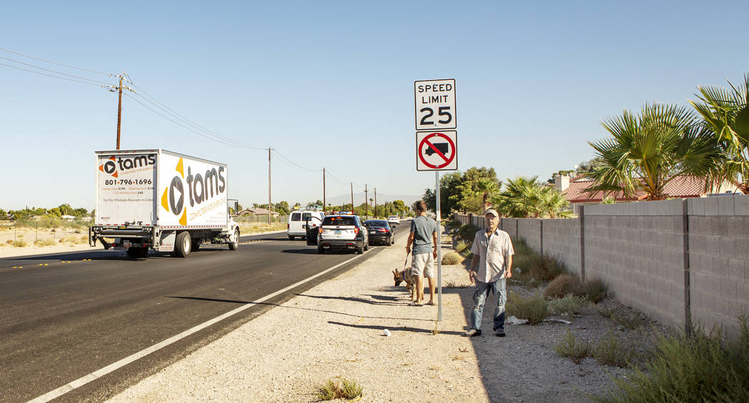 A truck driver drives by a no truck-zone lane as an officer pulls over a driver for speeding wh ...