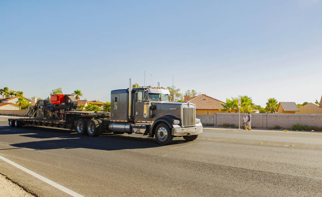 A truck drives through a no-trucks zone as Trevor Schneider and Jim Ludwick, background, watch ...