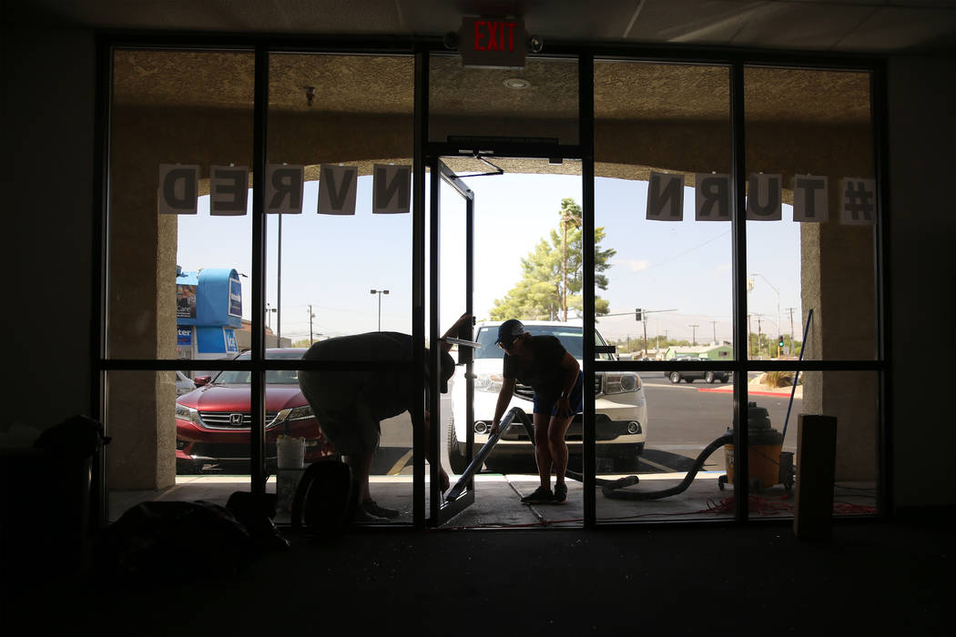 Volunteers Richard MacLean, left, and Diana Gomez, clean up shattered glass after a break-in to ...